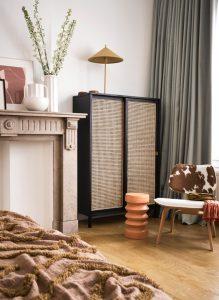 Der Schrank im Wiener Geflecht von Hk Living wird zu grauen Vorhängen und bunten Bildern kombiniert